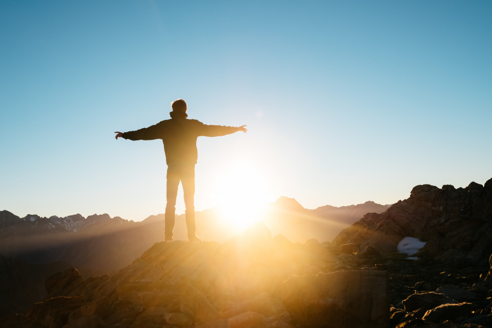 Person on top of hill with arms outstretched with sunrise in background