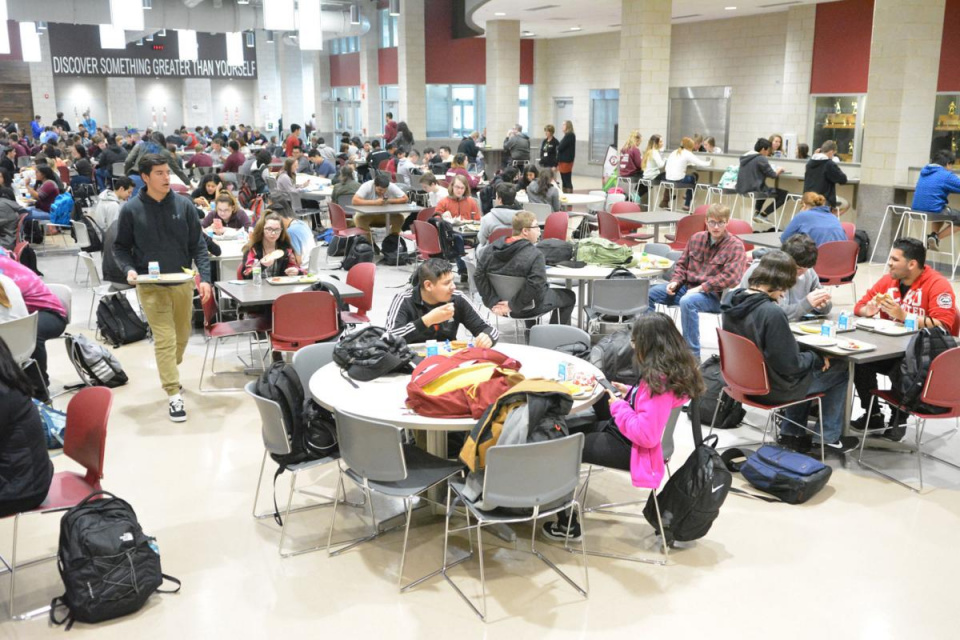 groups of students eating in a lunch room